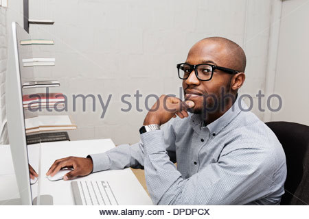 Portrait of young man using computer in design office - Stock Photo