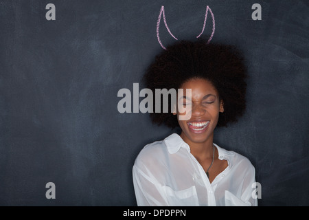 Young woman by blackboard with horns - Stock Photo