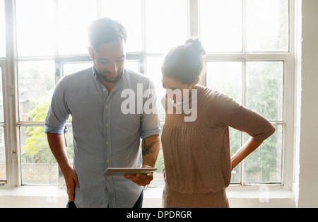 Mid adult couple using digital tablet - Stock Photo