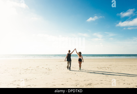 Young couple walking on San Diego beach, holding hands with arms raised - Stock Photo