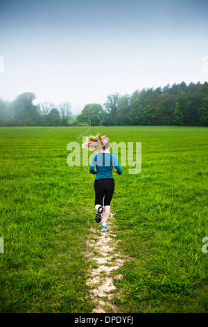 Mature woman running in countryside - Stock Photo