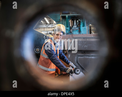 Engineer portrait in factory viewed through hole in steel - Stock Photo
