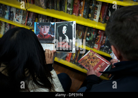 A foreigner (right) buys pirated movie DVDs in a store in Sanlitun, Beijing, China. 11-Jan-2014 - Stock Photo