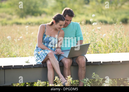 Couple sitting on countryside boardwalk with laptop computer - Stock Photo