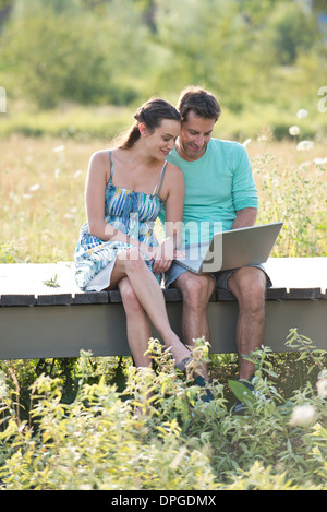 Couple sitting on countryside boardwalk using laptop computer - Stock Photo