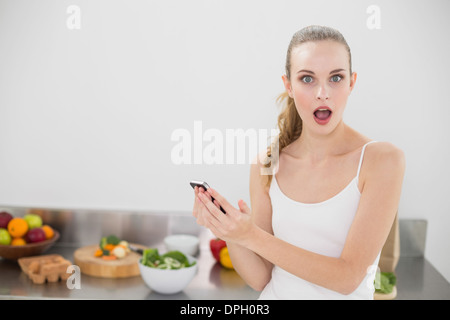 Shocked young woman holding smartphone looking at camera - Stock Photo