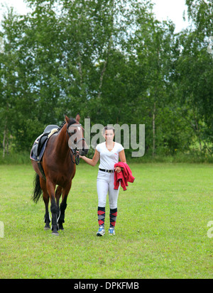 A pretty girl walks with her horse towards the camera - Stock Photo