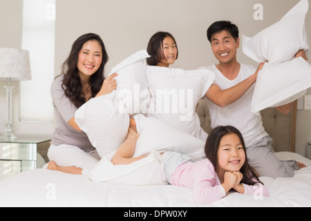 Family of four having pillow fight on bed - Stock Photo