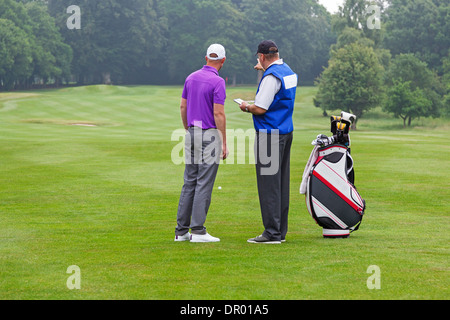Caddy pointing out a hazard to the golfer on a par 4 fairway - Stock Photo