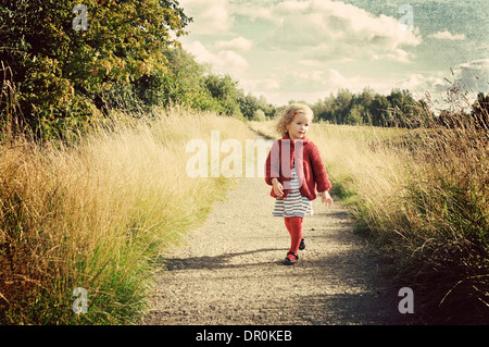 Little girl walking along path in countryside. - Stock Photo