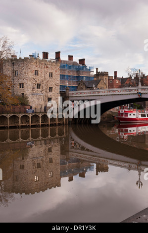 Lendal Bridge, stone Tower & moored city cruise boat reflected in water & seen from south bank of River Ouse - York, - Stock Photo