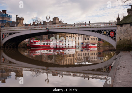 Iron bridge (Lendal Bridge) & moored city cruise boats reflected in water & seen from south bank of River Ouse  - Stock Photo