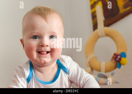 Portrait of a six month old baby boy looking curious at the camera - Stock Photo
