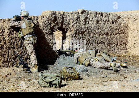 U.S. Marines soldiers take cover during a patrol in Helmand province, Afghanistan - Stock Photo