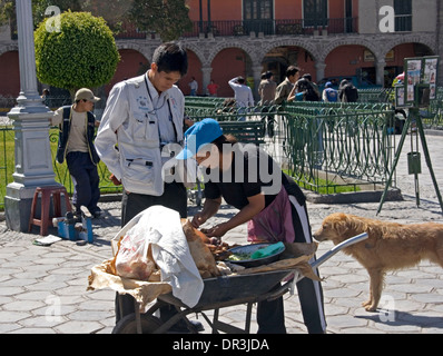 Street vendor selling cooked meat in wheelbarrow to customer in centre of city of Ayacucho in Peru - Stock Photo