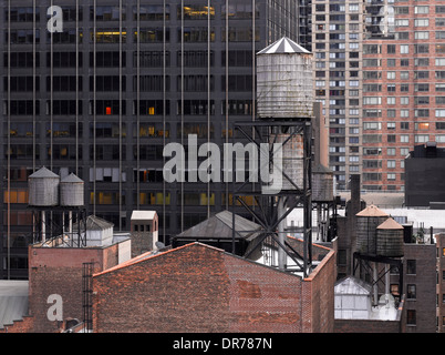 Water towers on rooftops with backdrop of high rise, New York, New York. - Stock Photo