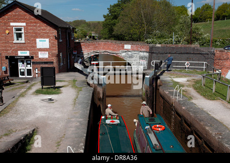 Two narrowboats entering the staircase locks at Bunbury on the Shropshire Union Canal, a base for Anglo Welsh boat - Stock Photo