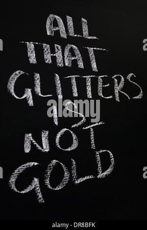 chalk writing- All that glitters is not gold.- words written on a blackboard. - Stock Photo