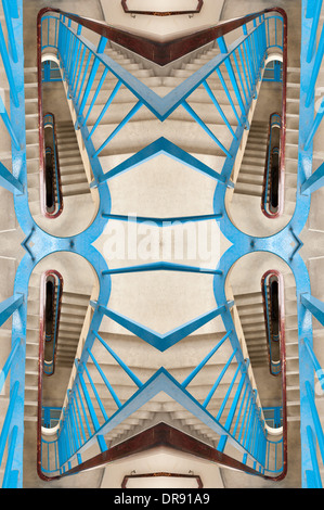 Vertigo anxiety and fear of heights a 6 floor stairwell trapped with steel blue handrail and dark and dingy flight - Stock Photo