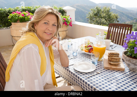 Senior woman eating breakfast at table on balcony - Stock Photo