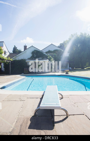 Diving board at edge of swimming pool - Stock Photo