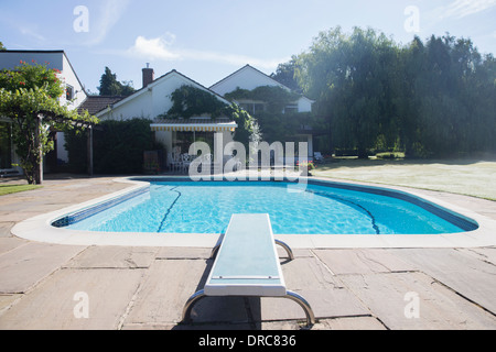 Diving board at the edge of swimming pool - Stock Photo