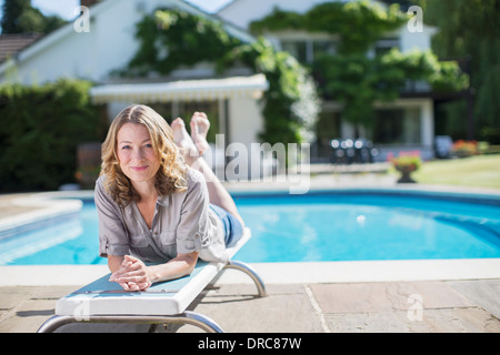 Woman laying on diving board at poolside - Stock Photo