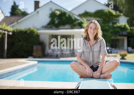 Woman sitting on diving board at poolside - Stock Photo