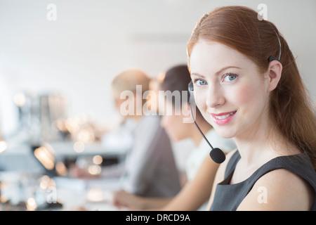 Businesswoman wearing headset in office - Stock Photo