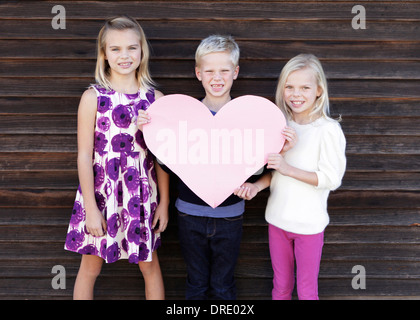 Siblings holding up large paper heart - Stock Photo