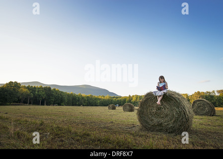 New York state USA hay bales girl sitting on the top of bale - Stock Photo