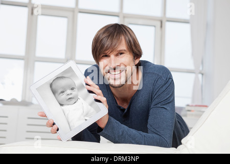 Germany, Munich, Man lying on sofa, holding digital tablet with photograph of newborn - Stock Photo