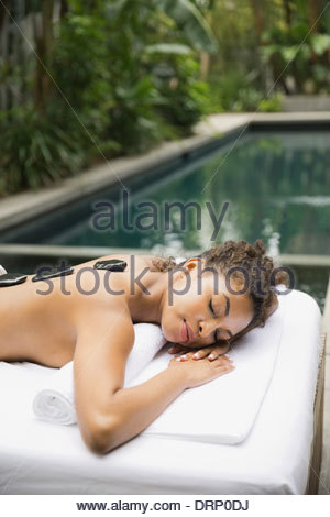 Relaxed woman receiving stone therapy at day spa - Stock Photo