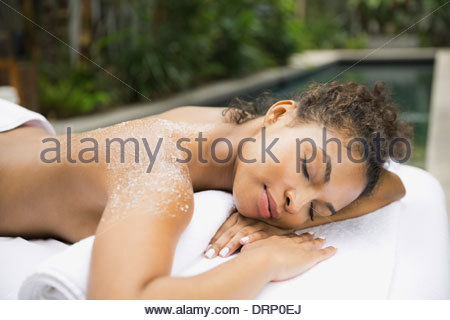 Relaxed woman at day spa receiving body scrub - Stock Photo
