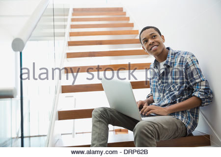 Teen using laptop on steps at home - Stock Photo