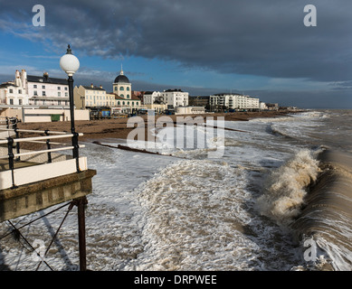 Waves crashing onto the beach, with seafront buildings and part of the pier bathed in warm light in winter, at Worthing, - Stock Photo