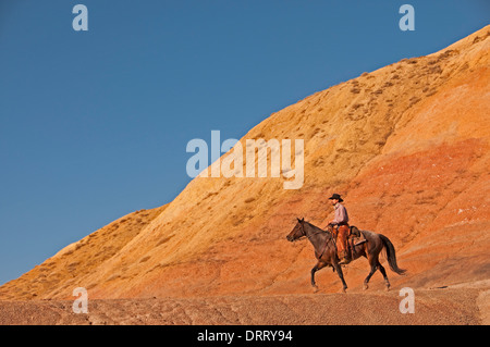 Cowboy rides his horse in the Painted Hills area of the Bighorn Mountains of Wyoming - Stock Photo