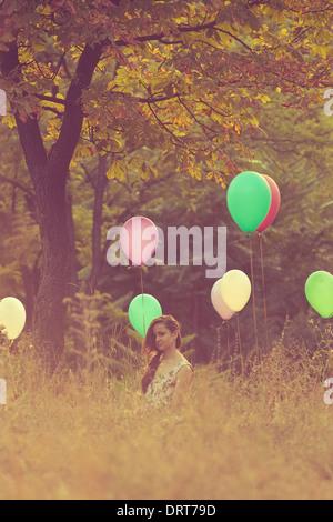 Girl sitting on balloons field - Stock Photo