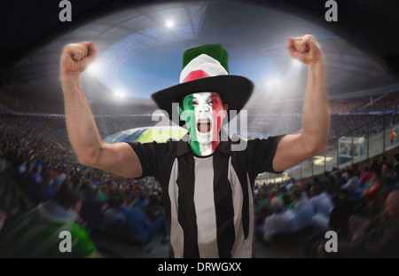 An Italian football fan celebrating a goal in a football stadium. - Stock Photo