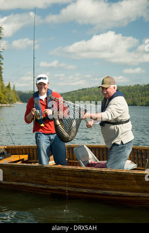Father and son anglers netting a large northern pike from their boat in a lake in Northern Ontario - Stock Photo