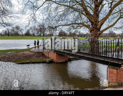 Young couple and dog walk near Old Deer Park footbridge  after heavy Winter rainfall - Richmond upon Thames, Surrey, - Stock Photo