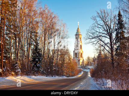 Beautiful winter sunset in the forest and church - Stock Photo