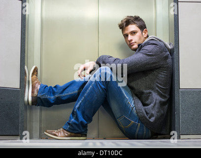 Handsome young man sitting in front of elevator (lift) doors, looking at camera - Stock Photo