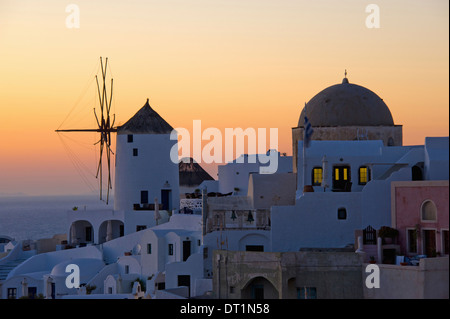 The historic white washed houses windmills and domed church of Oia town on Santorini island - Stock Photo