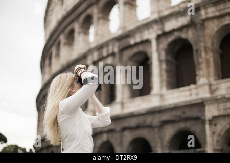 A woman outside the Colosseum amphitheatre in Rome taking photographs - Stock Photo