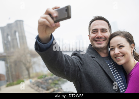 New York city The Brooklyn Bridge crossing over the East River A couple taking a picture with a phone a selfy of - Stock Photo
