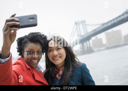 The Brooklyn Bridge crossing over the East River A couple two women taking a picture with a phone a selfy of themselves - Stock Photo