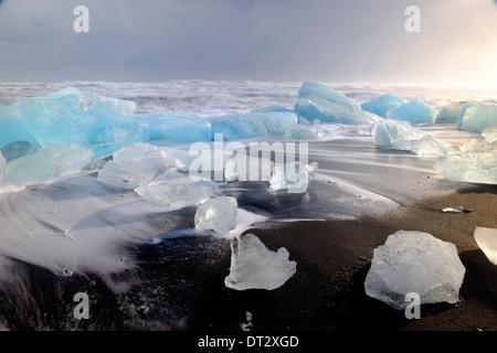 IceBergs and waves on Jokulsarlon Beach, Polar region, South Iceland - Stock Photo