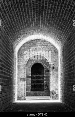 Brick-lined tunnel leading to an entrance in a Civil War Era fort. Converted to black and white. - Stock Photo