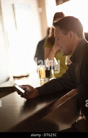 Businessman looking at cellphone in a wine bar - Stock Photo